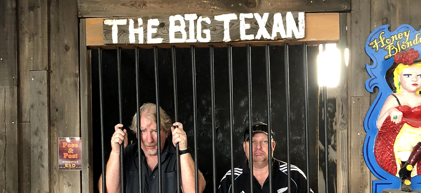 "Greg and Brett standing in the ""jail"" at The Big Texan restaurant."